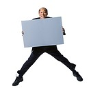 Portrait of a businessman holding a blank sign and jumping