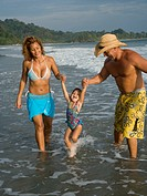 Parents playing with young daughter on beach