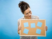 Woman holding a bulletin board with blank sticky notes