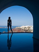 Woman in swimsuit standing at edge of infinity pool rear view
