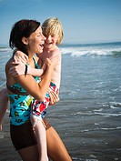 Young woman with little brother at beach