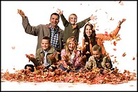Family posing in a pile of fallen leaves