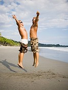 Two males jumping on the beach