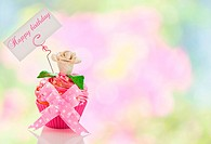 A beautiful pink happy birthday cupcake with flower and a label