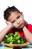 Boy with plate of broccoli frowning