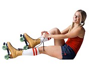 Portrait of young woman tying roller skates