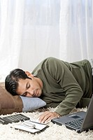 Man sleeping on cushion with laptop