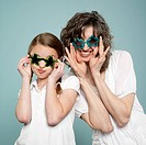 Studio shot of mother and daughter 10_11 wearing star shaped sunglasses