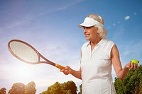 Senior woman with tennis racket and ball