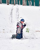 Boy building snowman with green leaf hands winter holidays