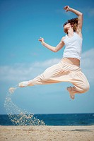 Teenage girl dancing hip_hop and jumping on beach, summer series