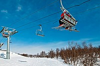 Chair lift with skiers on a blue sky