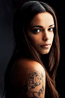Gorgoeous young hispanic woman gazing at you over her tattooed shoulder