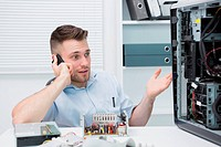 Computer engineer on call as he gestures towards an open cpu
