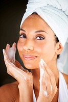 Portrait of a young ethnic woman taking care of her face