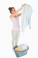 Woman examining shirt with laundry basket