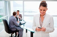 Colleagues in meeting with business woman text messaging in foreground