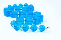 Blue glass beads on white background