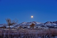 Setting moon with partial eclipse over the Chupadera Range, Bosque del Apache NWR, New Mexico, USA