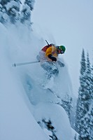 A man skiing deep powder while backcountry skiing at Sol Mountain, Monashee Backcountry, Revelstoke, BC