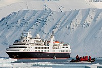 Zodiacs filled with tourists disembark from a cruise ship to view a polar bear sow and cub resting on Andoyane island, Liefdefjorden, northwest Svalba...