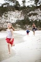 Woman and two girls running along beach, Cala de s Almunia, Santanyi, Majorca, Balearic Islands, Spain