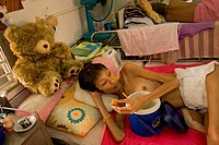 A transvestite with AIDS at the Buddhist hospice in Lopburi City, Thailand. Buddhist monks visit AIDS patients daily. Patients receive the anti retrov...