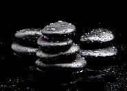 Spa Stones. black shiny zen stones with water drops over black b
