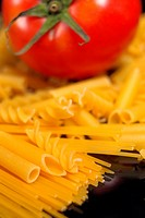 Italian pasta selection and tomato over black