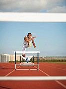 Boy 12_13 hurdling on running track