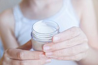 Close up of girl holding pot of lotion