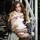 Woman holding large cat outdoors