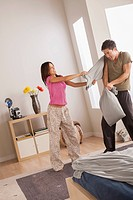 Couple having pillow fight in bedroom
