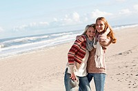 Smiling women hugging on beach