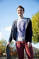Portrait of young man with skateboard smiling against sky