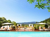Swimming pool with striped chaise lounge chairs and umbrellas at a luxury resort overlooking Napa Valley, California