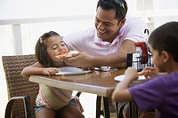 Hispanic father helping daughter to eat pizza