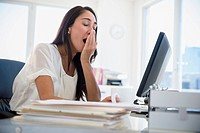 Caucasian businesswoman yawning at desk