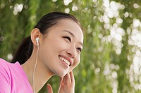 Smiling Chinese woman listening to music