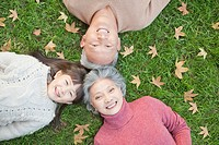 Chinese couple laying in grass with granddaughter