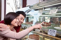 Chinese couple looking at cake in display case
