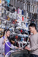 Chinese worker helping man with wheel in bike shop