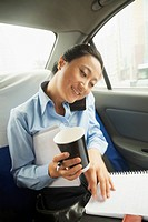 Chinese businesswoman working in backseat of car