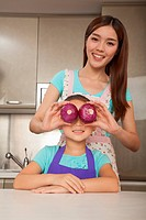 Chinese woman holding onions over daughter´s eyes