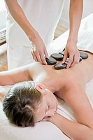 Woman having hot stone massage in spa