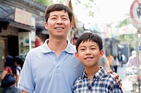 Chinese father and son smiling outdoors