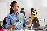 Black teacher holding digital tablet and chemistry model in classroom