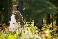 Mixed race woman wearing apron in field