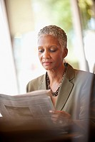 African American businesswoman reading newspaper in cafe
