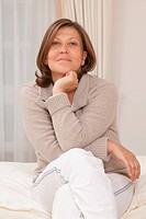 Potrait of a mature woman, sitting on bed